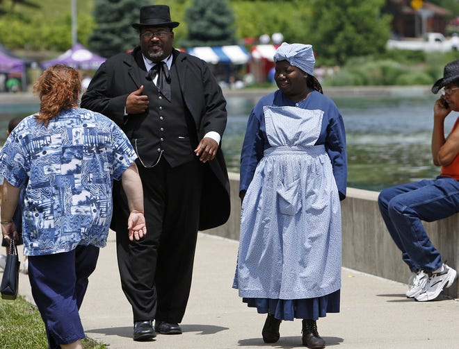June 14, 2008: (left to right) Chris Miller of Colerain Township playing the part of Rev. J.W. Loguen (King of the the Under Ground Railroad) and Novella Slaughter of Springboro playing the part of Miss Sadie, both with the re-enactors from the Freedom Center, participate in education portion of the Junteenth Festival, A Celebration of Freedom at Eden Park.