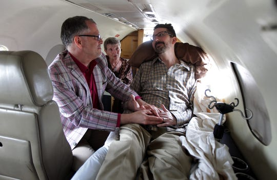 "Jim Obergefell, left, and John Arthur, who had ALS, wed on the tarmac of Baltimore/Washington International Airport on July 11, 2013. Paulette Roberts, center, officiated. ""I now pronounce you husband and husband,"" she announced."