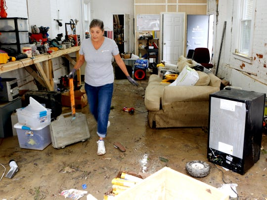 Sharon Ionna of Independence cleans out her business, SI Enterprises, on Lewis Street after several feet of water filled the workspace over the weekend. Ionna and her husband just moved their business into the building two months ago.