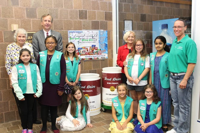 """On June 10th, Girl Scout Troop #60133 unveiled new """"BOBO Bins""""(Buy One Bring One) and signage at the Manville Library collection center."""