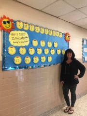 Jayne Kulyassa stands next to her last bulletin board after 33  years of teaching.