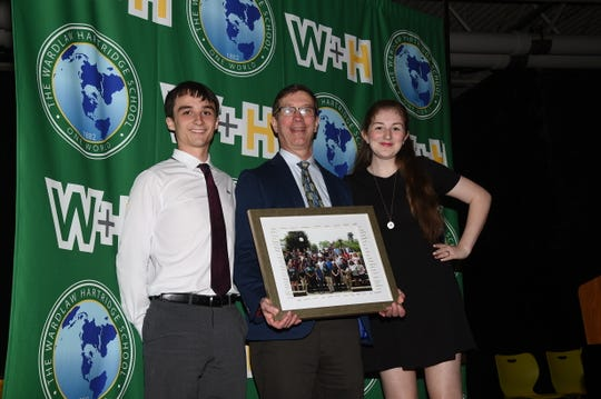 Dr. Bob Bowman of Scotch Plains receives the senior class photo from Kelton Estabrook of Plainfield and Alexandra Vargas of Dunellen.