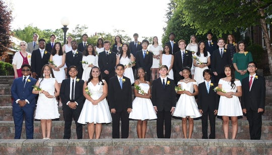 The eighth grade graduates gather for a class photo in the amphitheater.