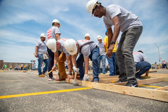 Jianfeng Li of China hammers in a nail as more than 600 Kemin employees from around the globe work with Habitat for Humanity to build 24 outdoor buildings for central Iowa families in the largest one day event in greater Des Moines Habitat for Humanity history outside the Community Choice Credit Union Convention Center Monday, June 17, 2019.