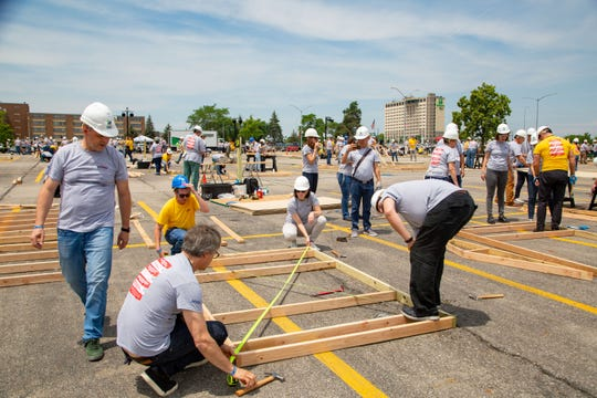 More than 600 Kemin employees from around the globe work with Habitat for Humanity to build 24 outdoor buildings for central Iowa families in the largest one day event in greater Des Moines Habitat for Humanity history outside the Community Choice Credit Union Convention Center Monday, June 17, 2019.