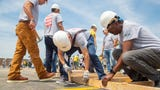 More than 610 Kemin employees from around the globe are building 24 outdoor buildings for Iowa families, the largest single-day event in Greater Des Moines Habitat for Humanity history.