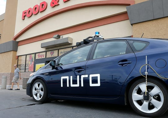 In this Aug. 16, 2018, file photo a self-driving Nuro vehicle parks outside a Fry's supermarket, which is owned by Kroger, as part of a pilot program for grocery deliveries in Scottsdale, Ariz. Domino's plans to test pizza delivery using fully autonomous vehicles in Houston. The world's biggest pizza company is teaming up with Nuro, a Silicon Valley startup that makes unmanned delivery vehicles.