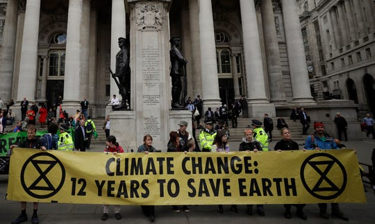 Extinction Rebellion climate change protesters hold up a banner near the Bank of England, in London in April.