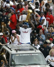 Ben Wallace raises the NBA championship trophy during the team's  parade in Detroit on June 17, 2004.