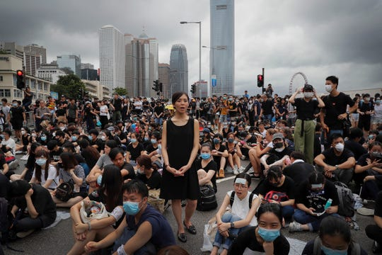 A protester, center, calls on Hong Kong Chief Executive Carrie Lam to step down as she and others continue protest against the unpopular extradition bill near the Legislative Council in Hong Kong, Monday, June 17, 2019.