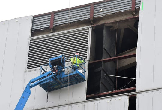 Detroit-based Adamo Group was hired to demolish the city-owned building, but a subcontractor is removing the exterior panels.