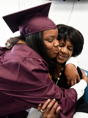Graduate Felicia Thompson, left, hugs her grandmother, Janice Dyer, after the commencement ceremony.