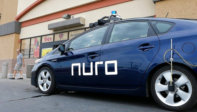 In this Aug. 16, 2018, file photo a self-driving Nuro vehicle parks outside a Fry's supermarket, which is owned by Kroger, as part of a pilot program for grocery deliveries in Scottsdale, Ariz. Domino's plans to test pizza delivery using fully autonomous vehicles in Houston.