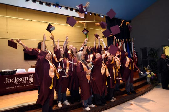 The new graduates at the Women's Huron Valley Correctional Facility in Ypsilanti throw their mortarboards into the air in celebration of receiving their associate degree diplomas from Jackson College.