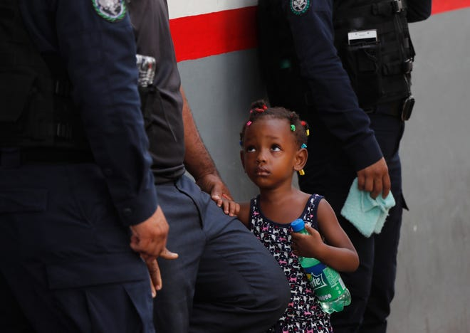Federal Police and migration officers hold a child after her mother tried to jump the line at an immigration center May 27 in Tapachula, Chiapas state, Mexico.