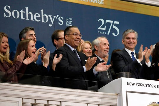Sotheby's Chairman Domenico De Sole, second from right, is applauded by CEO Tad Smith, right, and others as he rings the New York Stock Exchange opening bell March 11 to celebrate the company's 275th anniversary.