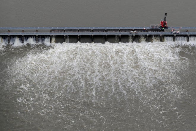 Workers open bays of the Bonnet Carre Spillway on May 10 to divert rising water from the Mississippi River to Lake Pontchartrain, upriver from New Orleans, in Norco, La.