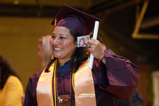 New graduate Dakota Shananaquet holds up her associate degree diploma from Jackson College, as well as a photo of her deceased daughter, Andrea Reese.