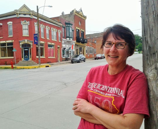 Judy Schwab is chairperson for the Oxford Sesquicentennial Committee in charge of the four-day celebration July 3-6.  She poses here in front of historic downtown buildings in this community of 825 persons.