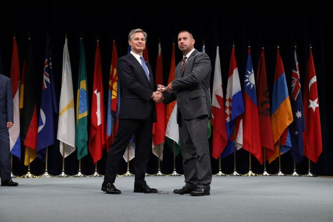 FBI Director Christopher Wray shakes Jackson Police Department Maj. Phillip Kemper's hand during Kemper's graduation from the FBI's 10-week National Academy program June 7, 2019, in Quantico, Va.