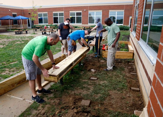 Volunteers put the finishing touches on one side of a raised garden bed being built at Gorsuch West Elementary Saturday, May 25, 2019, in Lancaster. Volunteers from the Vineyard Church and the school built three new raised garden bed. The new beds will give the school's garden club six beds to plant flowers, fruits and vegetable.