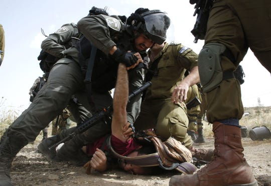 Israeli forces immobilize an activist.