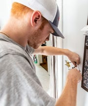 Apprentice Austin Bobille of Nelco Electric replaces a light switch as he and other volunteers upgrade the electrical service at the home of fallen Milwaukee Police Officer Michael J. Michalski on Saturday, June 15, 2019.