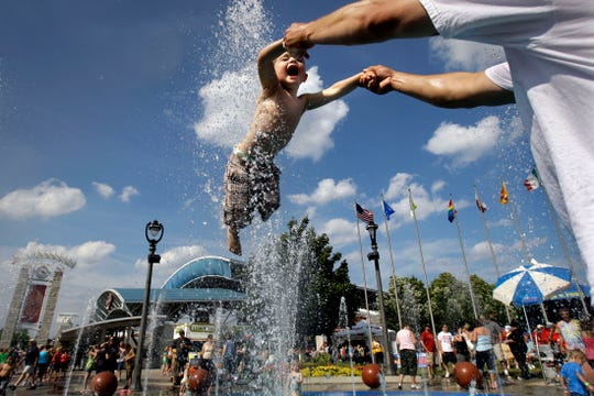 The water playground at the entrance to Summerfest was a popular place on June 25, 2010 with temperatures reaching the upper 80's. Jake Thorpe, 2, cools off as his dad A.J. Thorpe, both of Youngstown, Ohio, swings him through the jets of water.