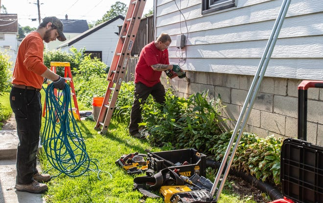 Joey Lococo (left) of Staff Electric and Steve Lococo of Pieper Electric work to upgrade the electrical service at the home of fallen Milwaukee Police Officer Michael J. Michalski on Saturday, June 15, 2019.