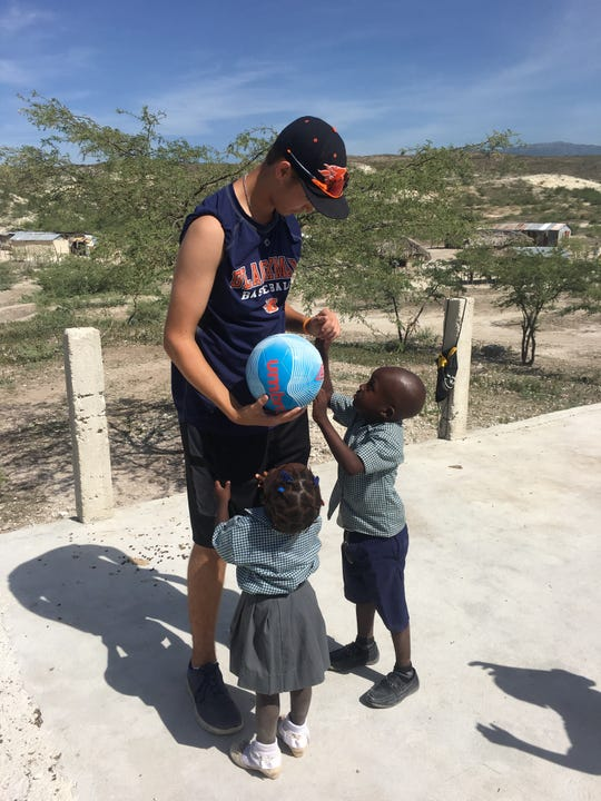 Tyler Battle works with children during a past trip to the Dominican Republic. The recent Blackman graduate will take a nine-month mission trip there starting in August.