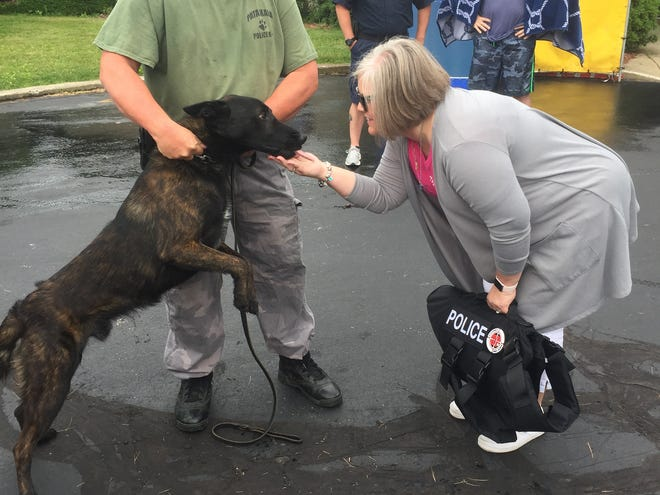 """Receiving a ballistic vest on June 15 from Christy Addington (right) is Pataskala K-9 Officer Demon with partner Randy Morton during the first of the """"Dog Days of Summer"""" fundraisers held in 2019."""