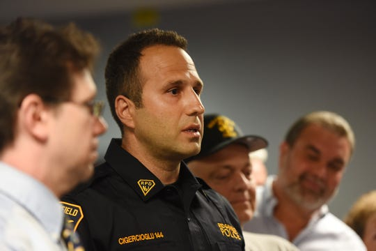 Ridgefield Police officer Hagop Cigecioglu (Center), who rescued a man from burning rubble, after an explosion obliterated the man's borough home, talks to the media as Mayor Anthony R. Suarez (L) and other officials listen during a press conference, photographed at Ridgefield City Hall on 06/17/19.