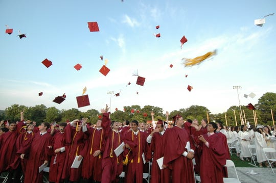 Students of a recent graduating class of Wayne Hills High School toss their caps in the air.