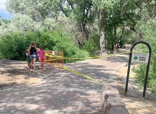 Weekend Berg Park visitors stop to read the warnings posted by the City of Farmington urging people not to walk on the park's riverfront paths due to dangers that include falling trees.