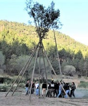 Tribal members prepare one of the large teepees for the ceremonial.