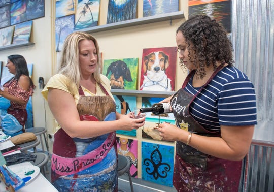 Talya Scott, right, pours a class of wine for Melissa Dewitte during a class at Painting with a Twist in Pensacola on Thursday, June 13, 2019.