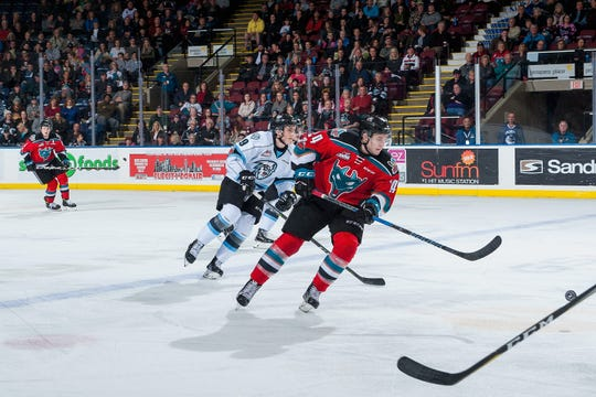 Kootenay Ice winger Peyton Krebs (19) skaes up the ice behind Kelowna Rockets center Kyle Topping during a game on Dec. 2, 2017.