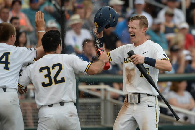 Michigan first baseman Jimmy Kerr (15) celebrates with infielder Joe Pace (32) after scoring in the third inning against the Texas Tech during a 2019 College World Series game at TD Ameritrade Park.