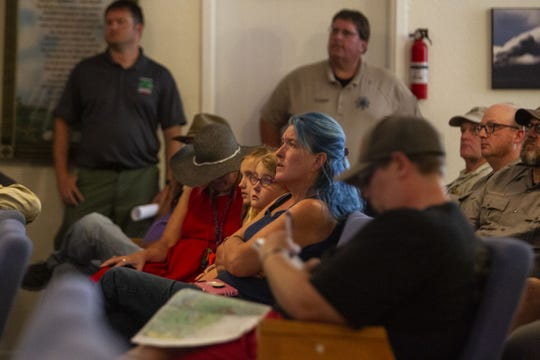 Sammi Jenkins (center) attends a meeting about the Woodbury Fire with her two daughters on June 16, 2019, at the Roosevelt Baptist Church. Jenkins' property is located in an area that is predicted to be impacted by the fire.