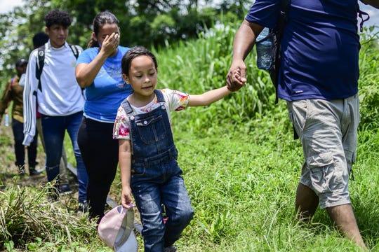 Migrantes de Honduras avanzan sobre un camino entre selva.