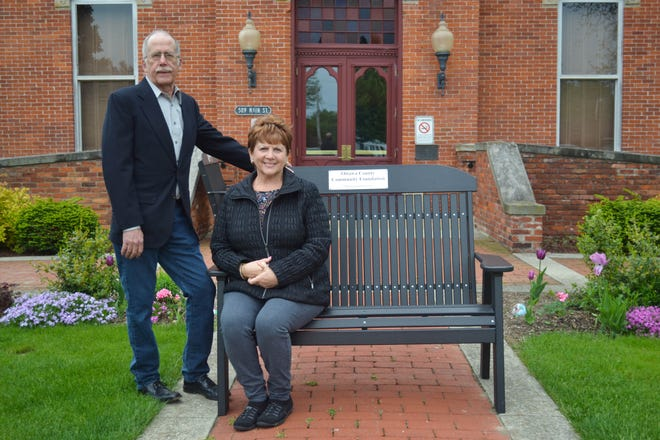 Genoa Garden Club member Kim Harsanje sits on one of the two Forever Benches the club purchased using grant money from the Ottawa County Community Foundation. Jon James, standing, said the benches fit with the foundation's guidelines for enhancing the community.