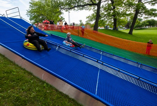 Port Huron Parks & Recreation Director Nancy Winzer, left, races against former director Betty Dunn on the Super Slide at Palmer Park Monday, June 17, 2019. The slides are free for anyone 4 and older.