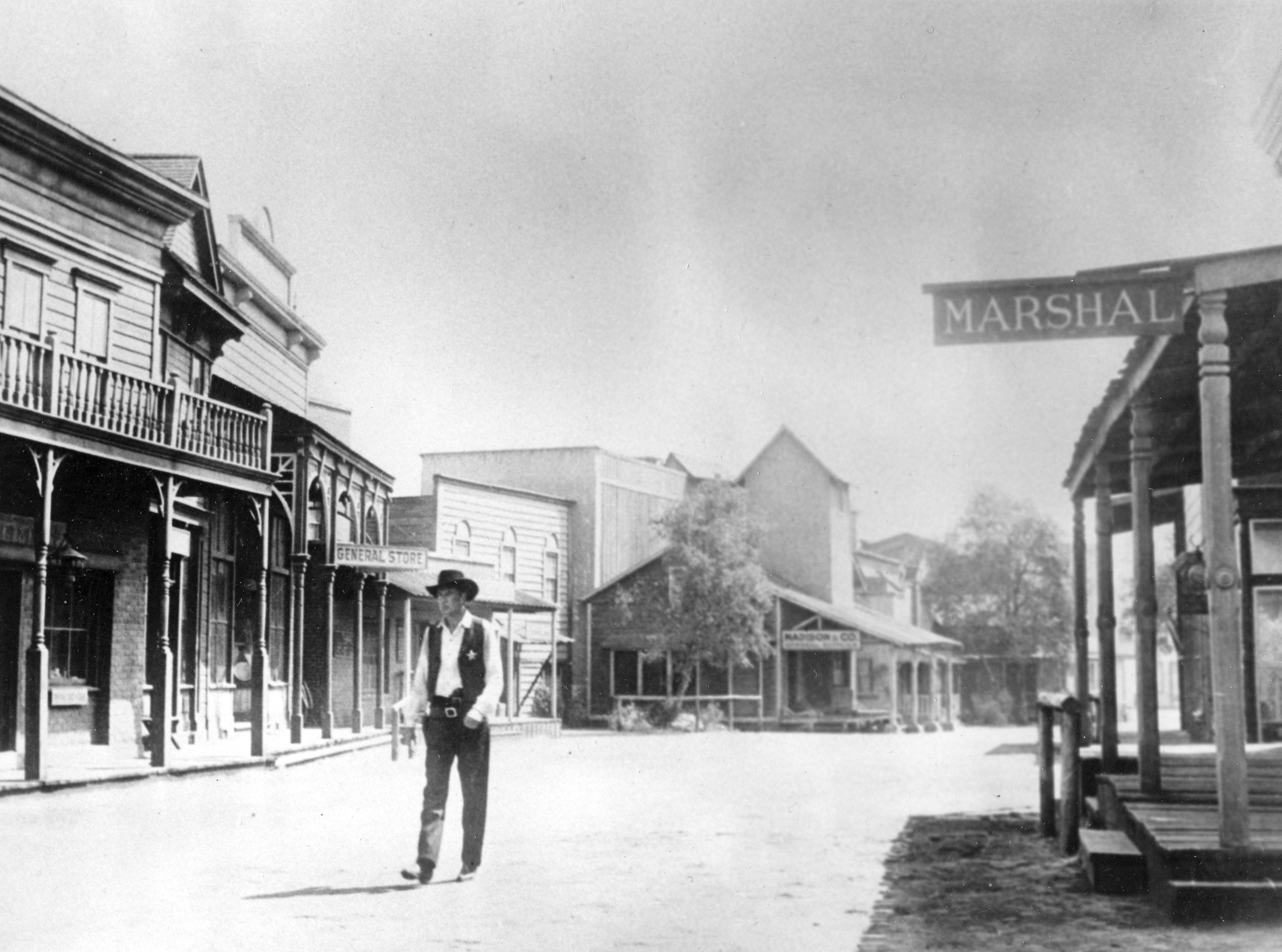 "Gary Cooper, portraying a sheriff, walks down a deserted street of a Western town on a Hollywood set in the 1952 movie ""High Noon."""
