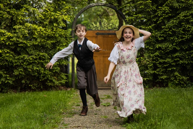 """Sean Mahoney, as Colin, left, and Janey Langan, as Mary Lennox, play a game of chase at the Beatrix Farrand Garden in Hyde Park in a photo shoot for Rhinebeck Theatre Society's production of """"The Secret Garden."""""""
