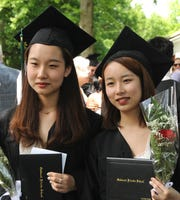 Twin sisters Xinli (Heidi) Wang, left to right, and Xinling (Clare) Wang are shown during Oakwood Friends School graduation June 7, 2019.