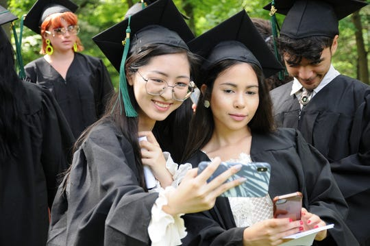 Yicheng (Annice) Liu of China and Mitashie (Mishy) Olmo of Puerto Rico take selfies during the 2019 Graduation at Oakwood Friends School, June 7.
