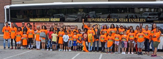 Harambee Reading Academy students, tutors, chaperones and guests prepare to board a bus to take them to the National Museum of African American History and Culture in Washington, D.C. earlier in June. Transportation was provided on the Gold Star Families bus.