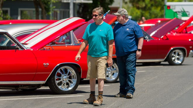 Car show attendees stroll past some of the classic cars on display.