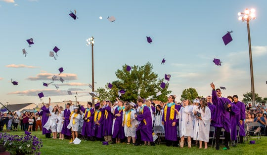 Graduating seniors toss their caps into the air at the close of the ceremony.