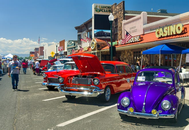Spectators walk by classic cars on display along Main Street.